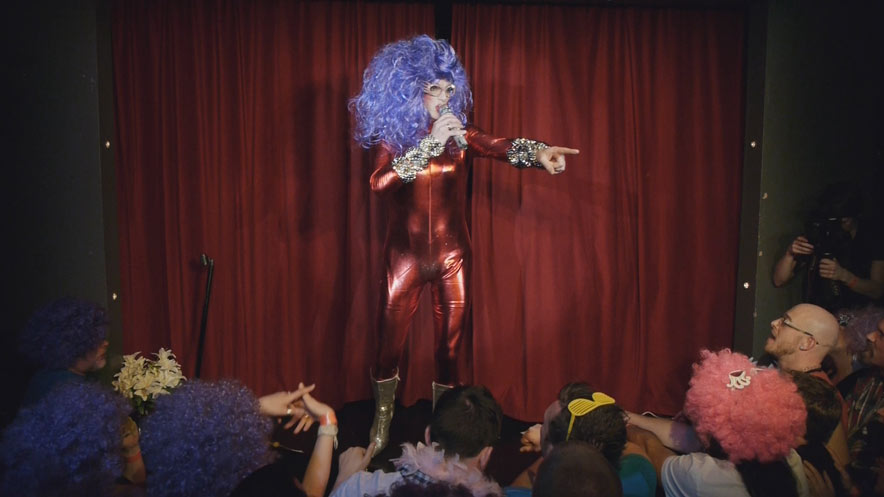 Live show video production. Dame Edna is wearing a red metallic one piece and a large purple curly wig.